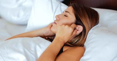 a woman wearing earplugs to help her sleep